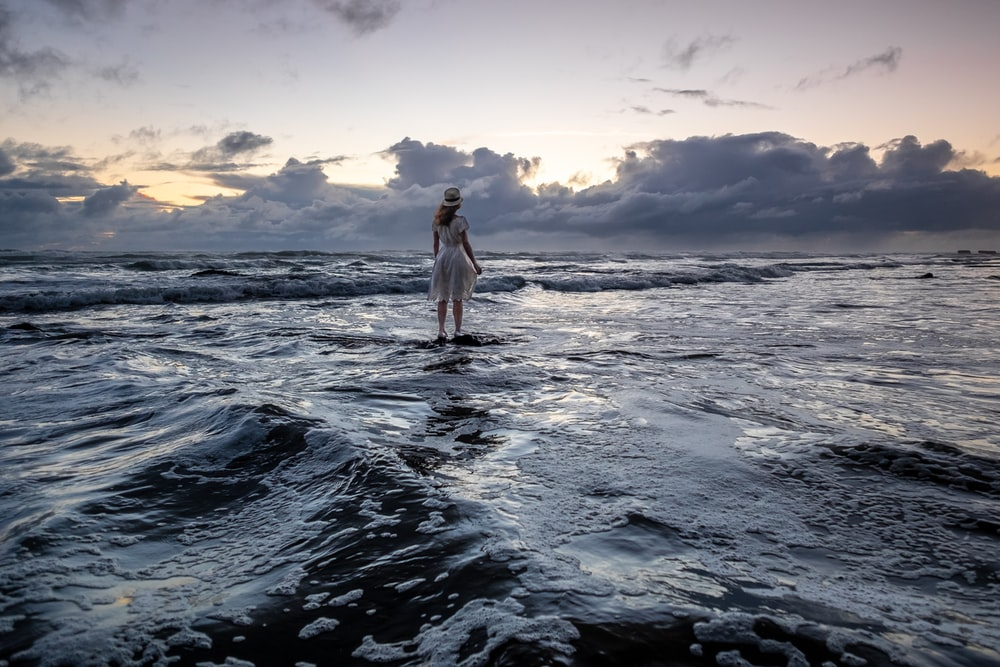 woman standing on seashore during sunrise