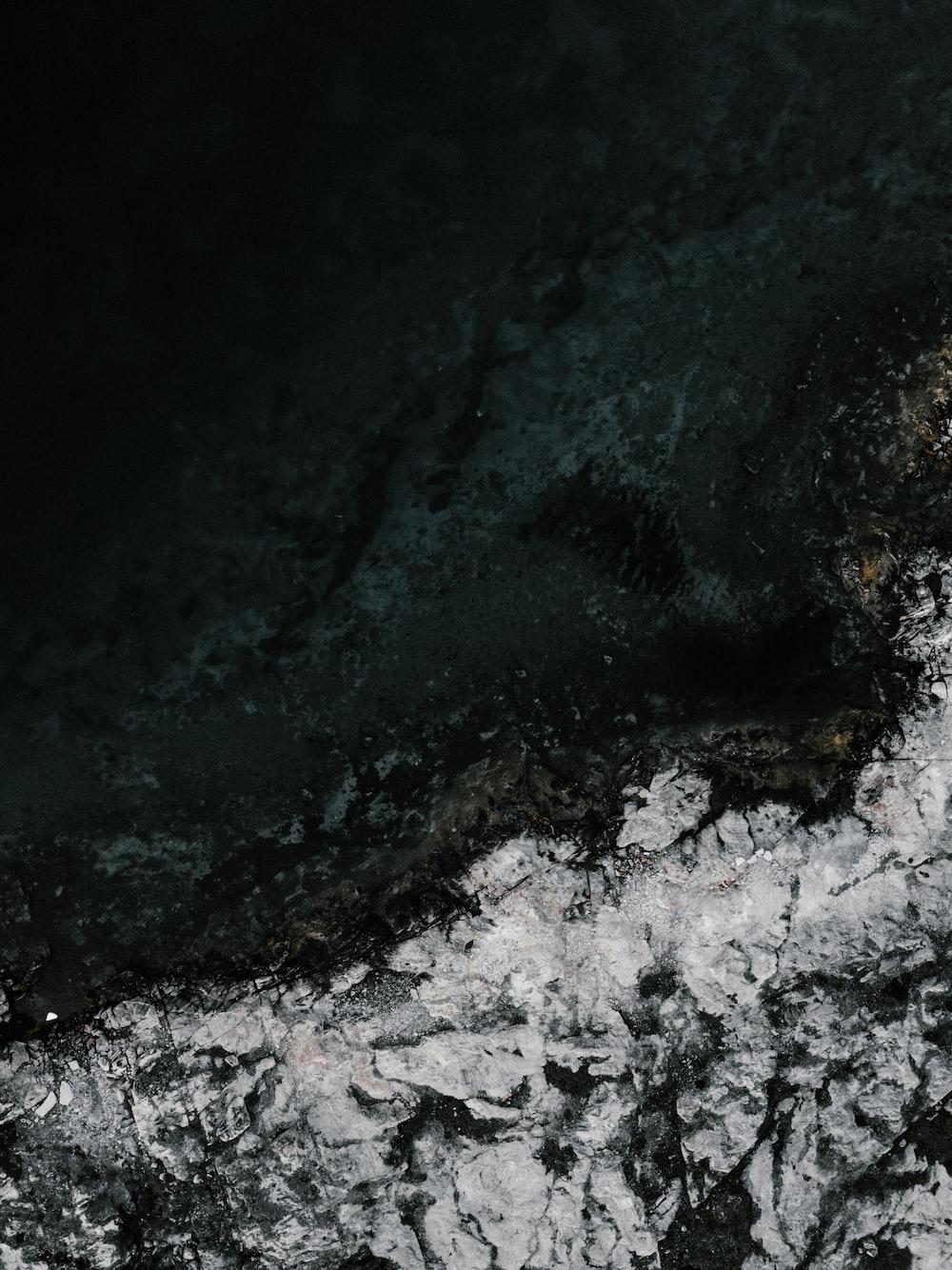 water crashing the cliff during nighttime