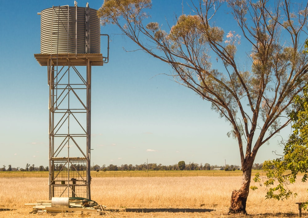 water tank tower placed on barren ground during daytime