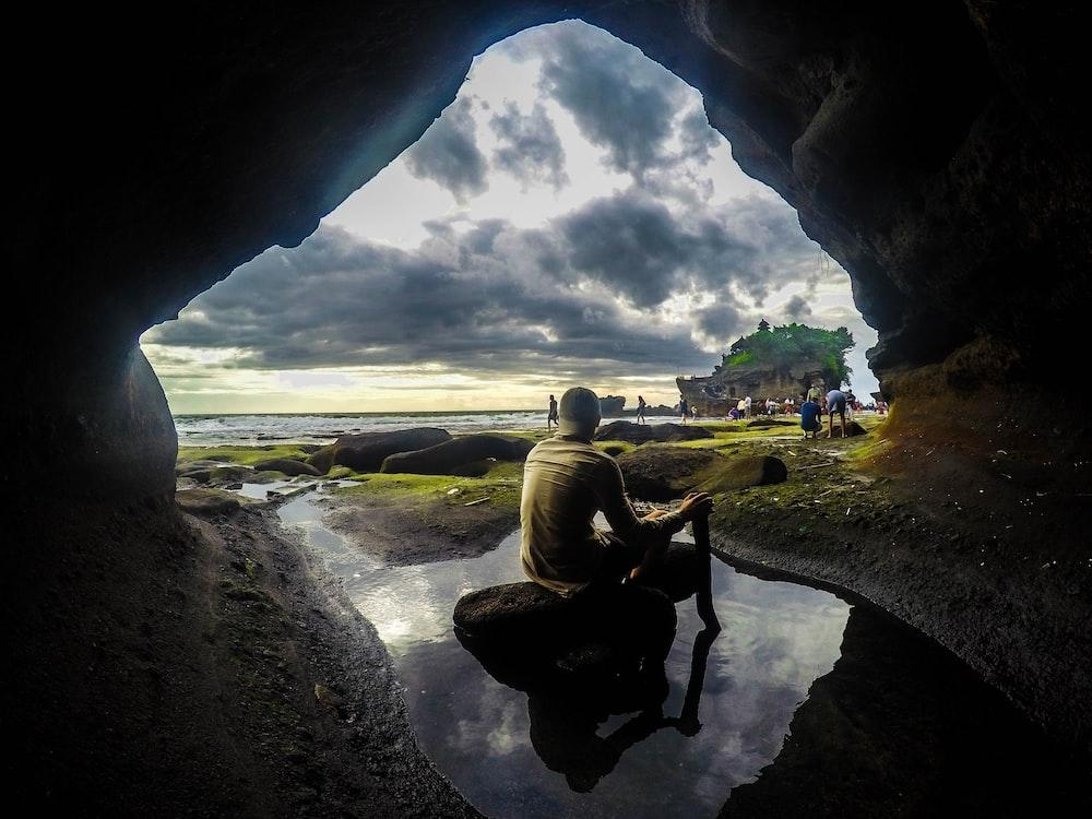 man sitting on stone during daytime
