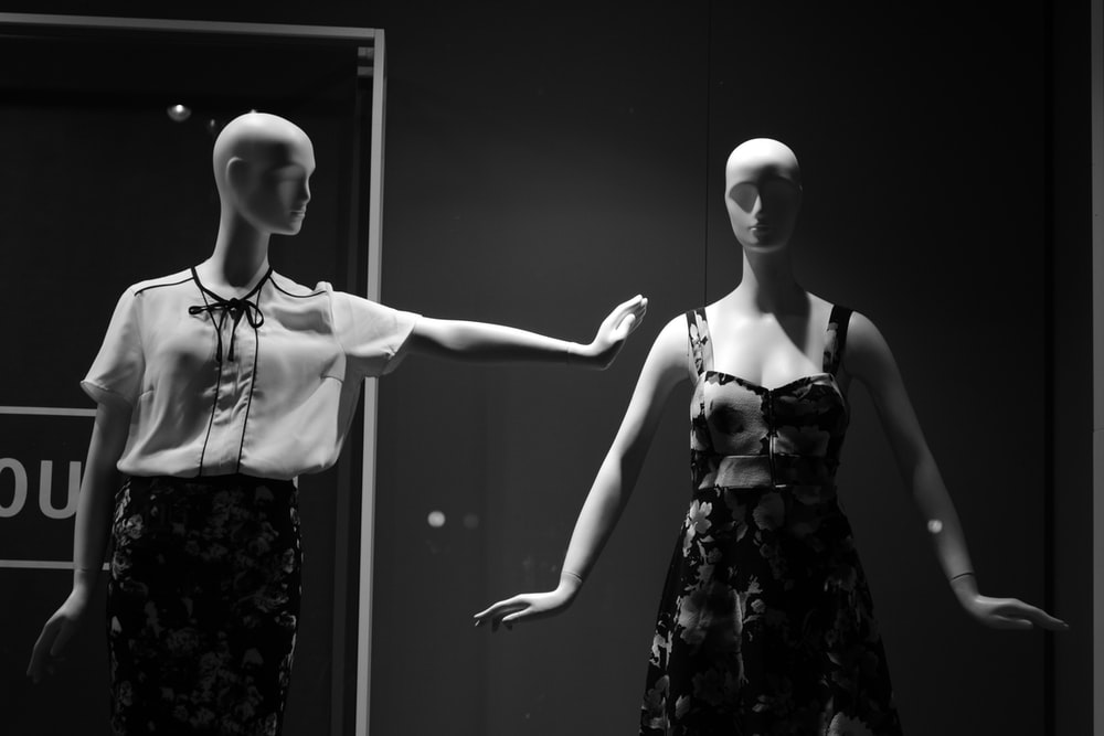 female dress form with white and black outfit beside female dress form in room