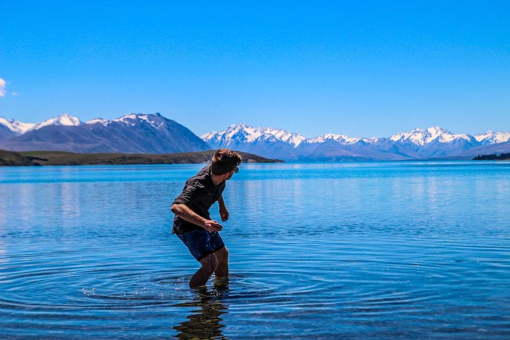 man throwing pebble on ocean water