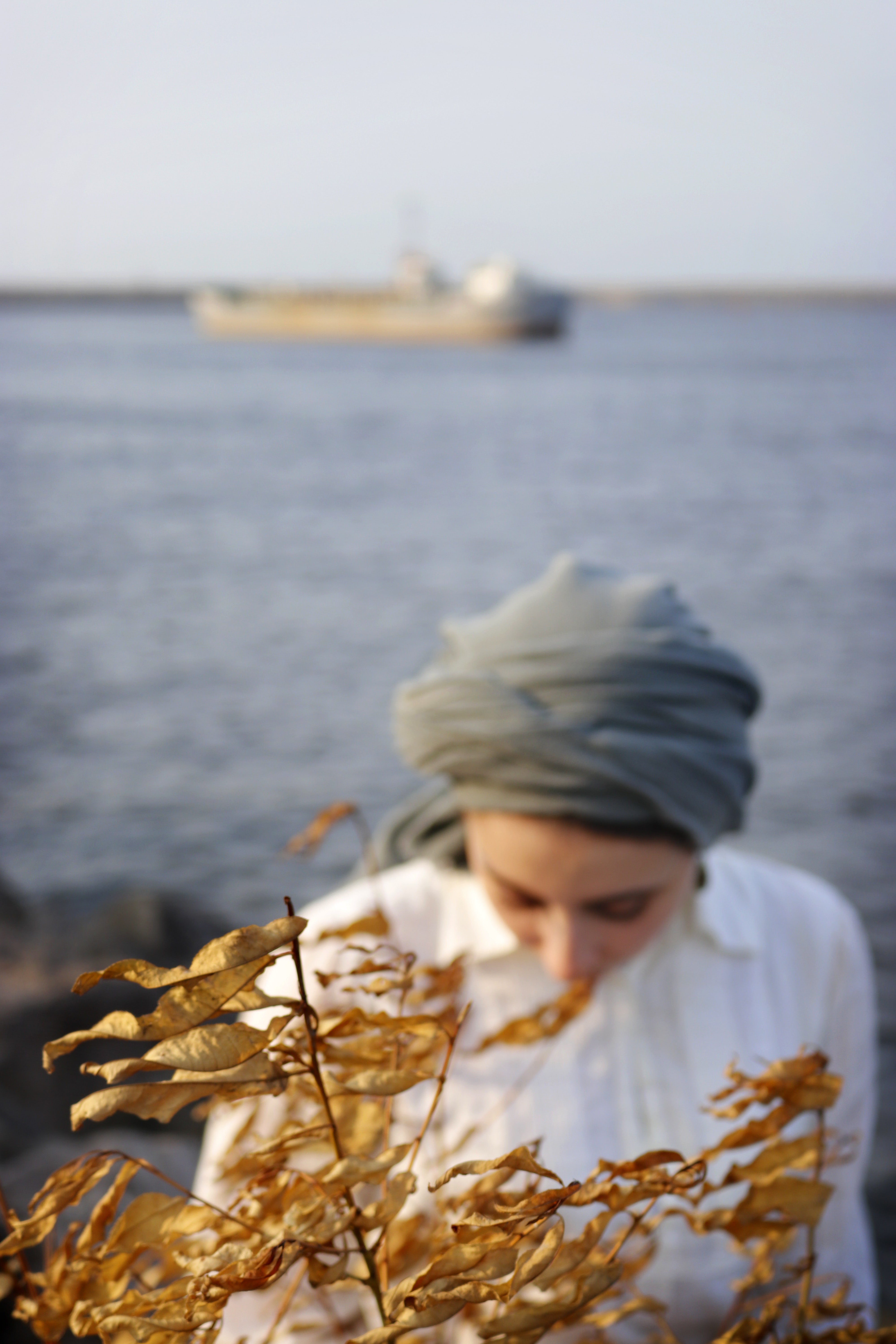 woman in white shirt behind brown leaves selective focus photography