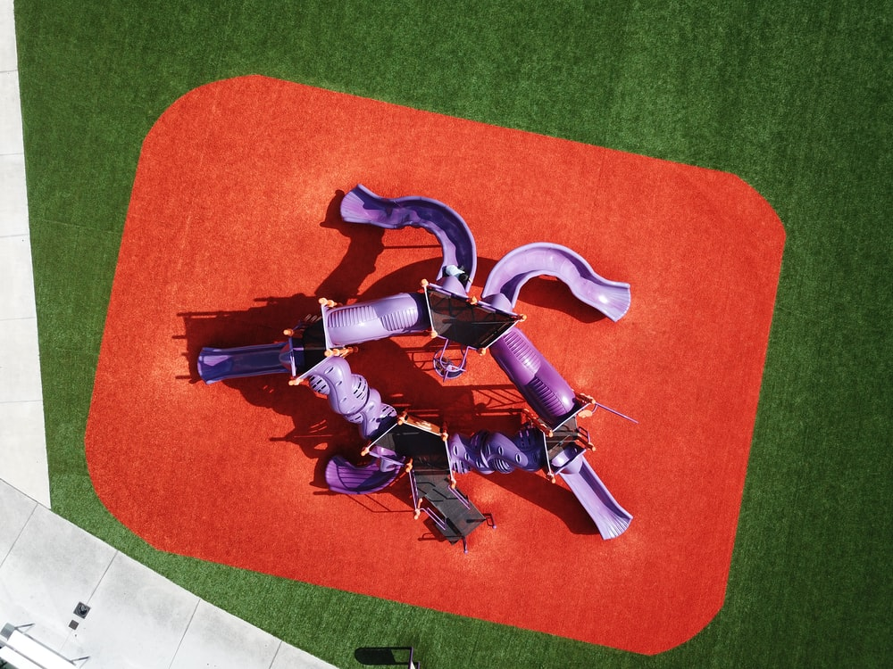 purple toys on orange and green textile surface
