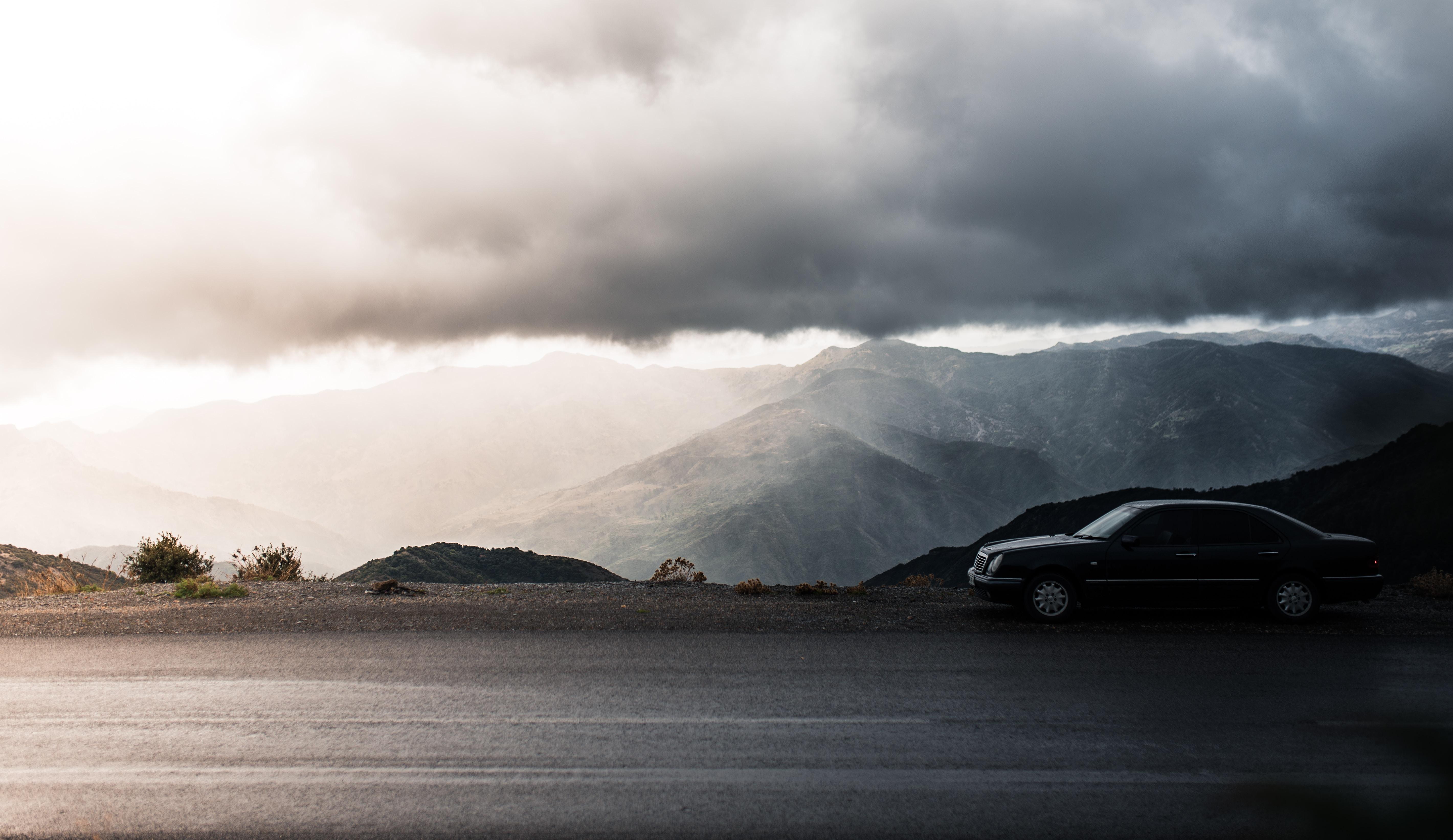black sedan parked beside road near mountain during daytime