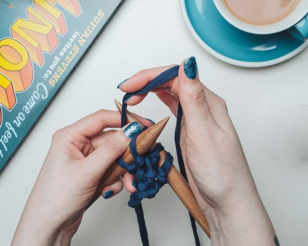 person tying blue lace on two brown sticks beside teal and white ceramic teacup set
