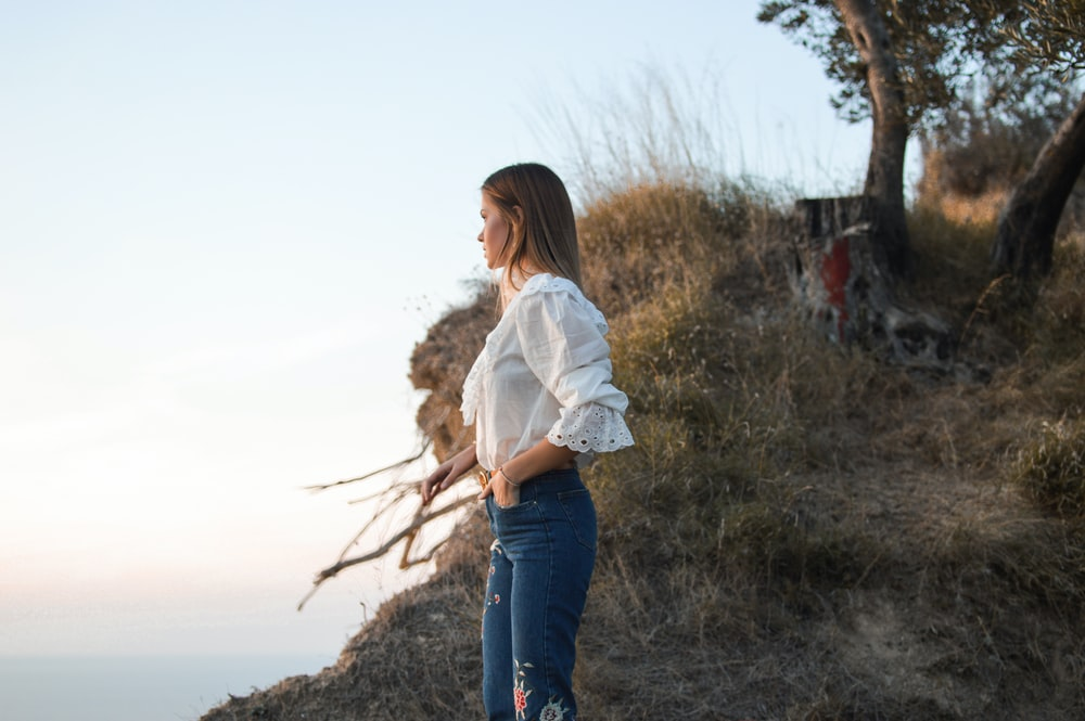 woman standing in mountain wearing white blouse watching body of water during daytime