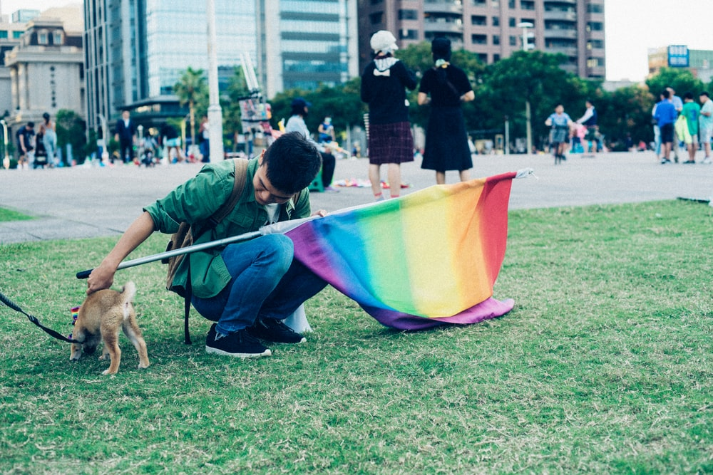 man holding multicolored flag and puppy during daytime
