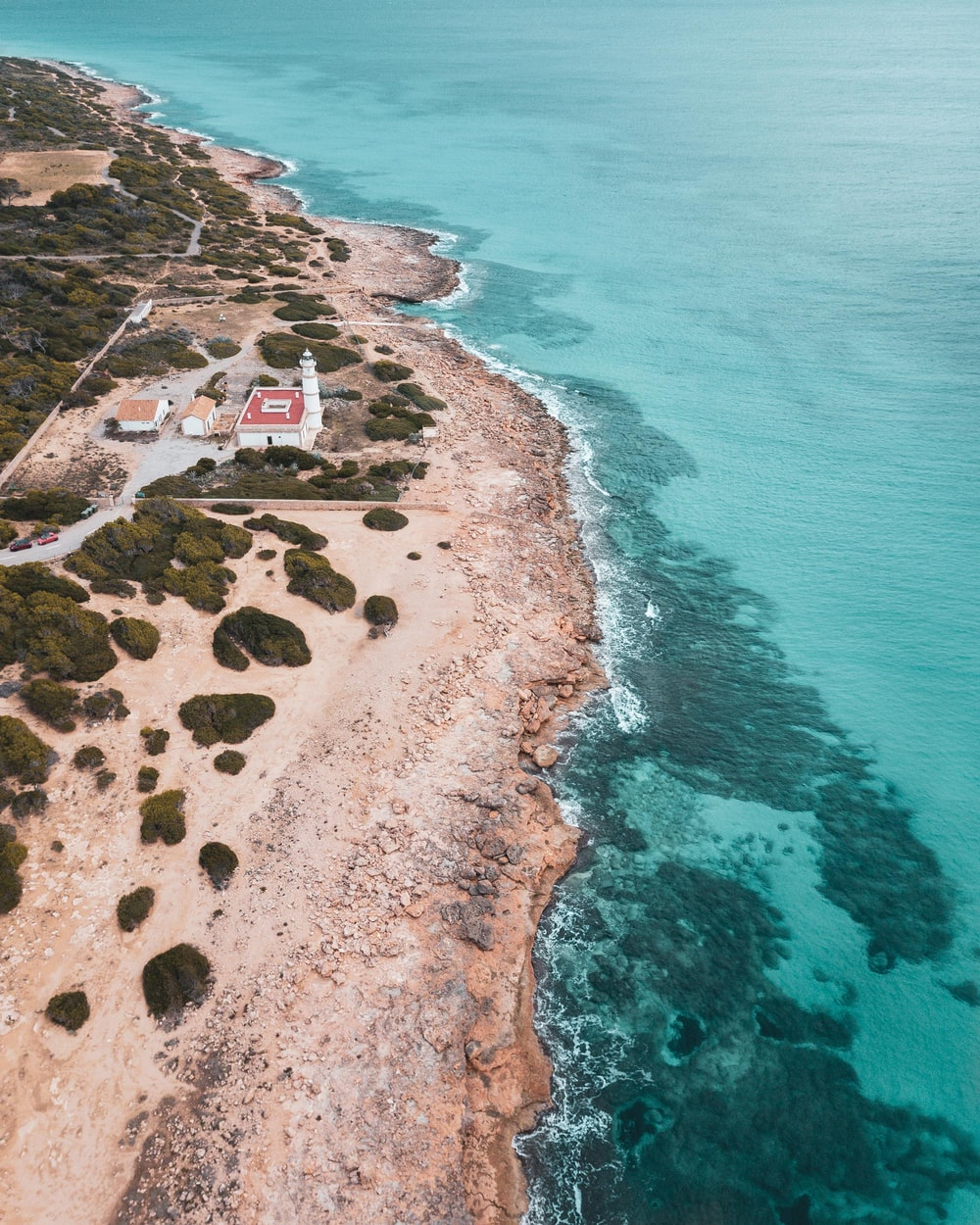 aerial photo of light house near body of water during daytime