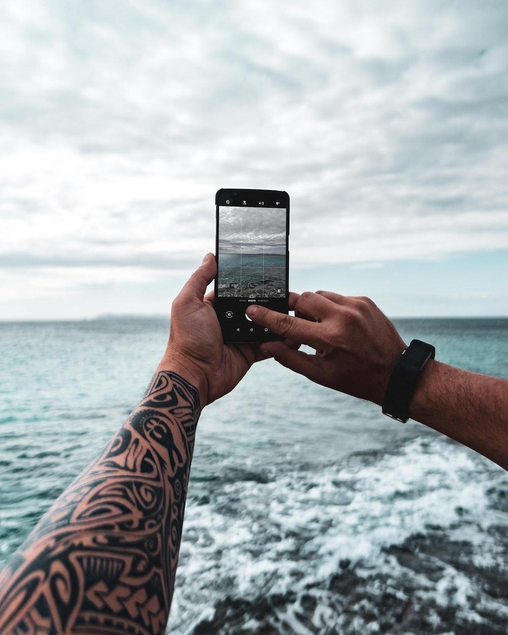person taking photo of calm sea
