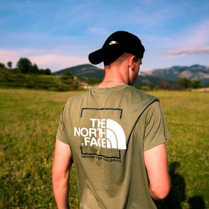 man in brown The North Face crew-neck shirt