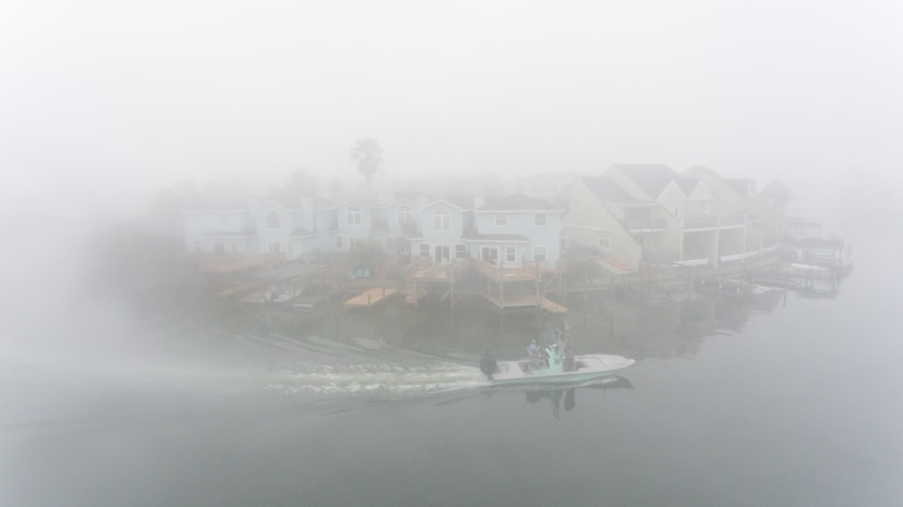 boat passing houses in foggy day
