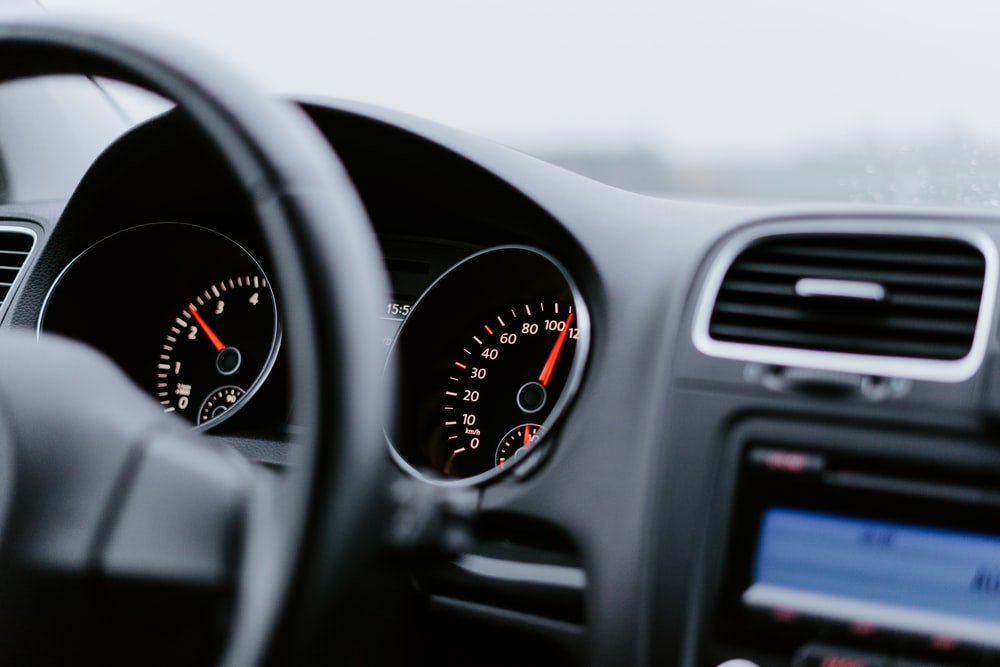 black vehicle dashboard with speedometer on 100