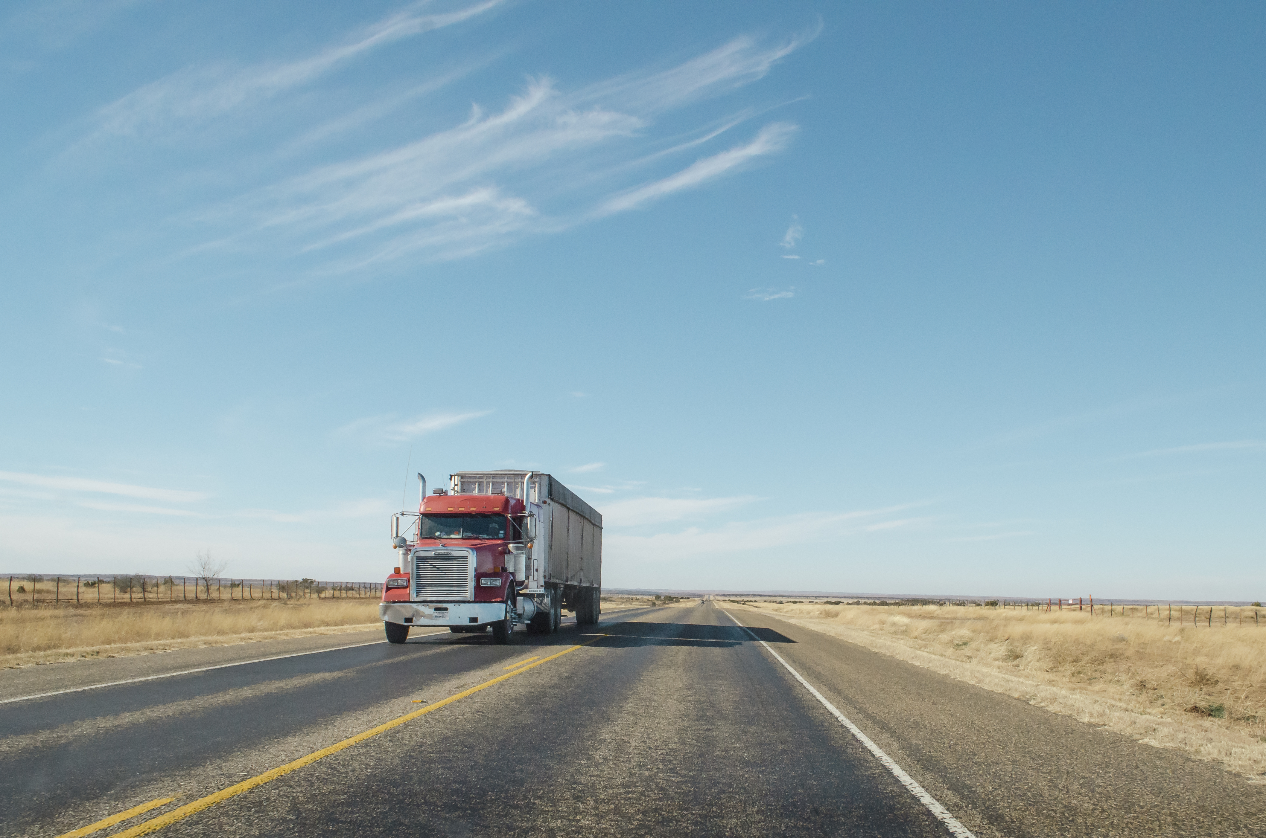 """""""A red semi truck driving along a West Texas road"""""""