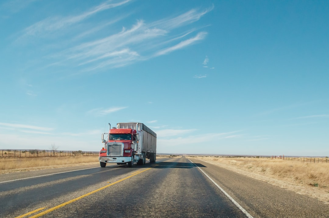 A red semi truck driving along a West Texas road