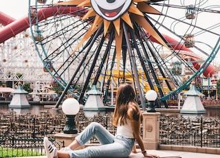 woman sitting on brown concrete table near ferris wheel