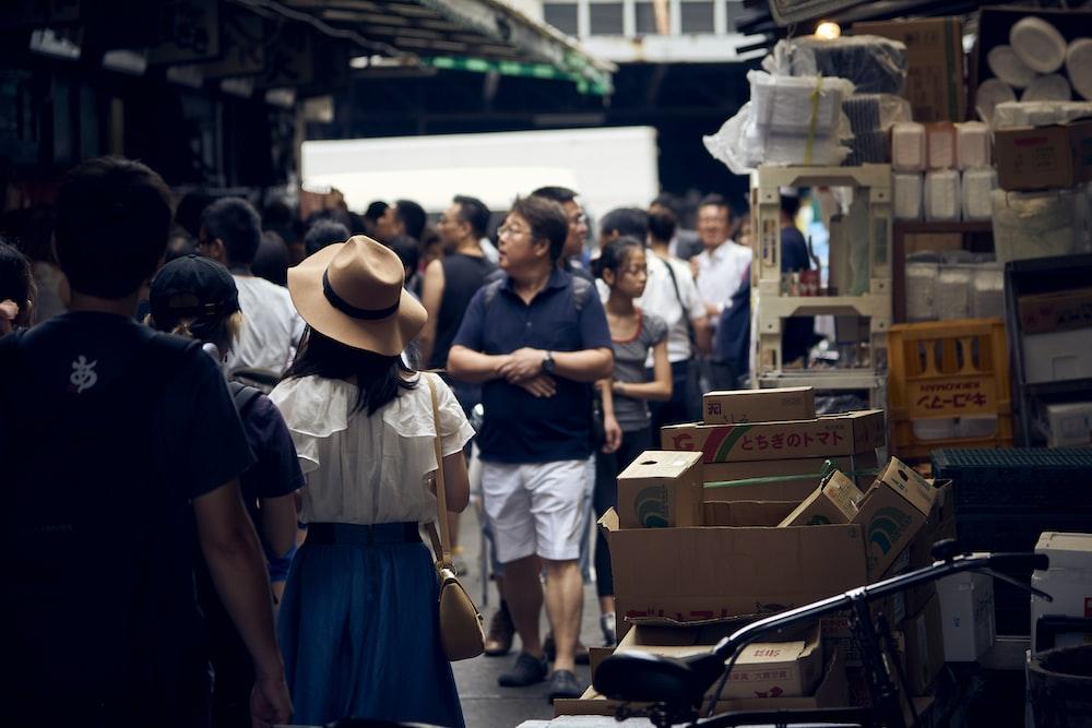 people walking on street near cardboard boxes during daytime