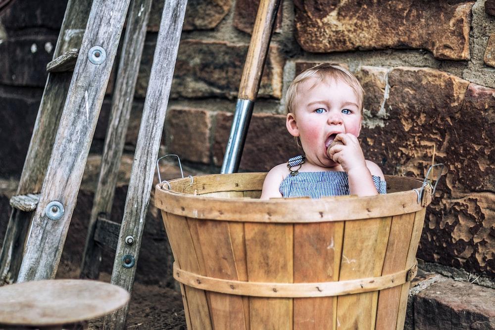girl in brown wooden bucket