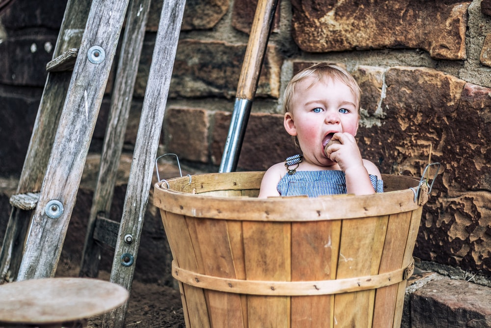 girl in brown wooden bucket