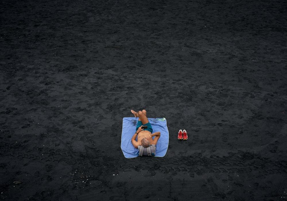 shirtless man lying on blue picnic mat on the field