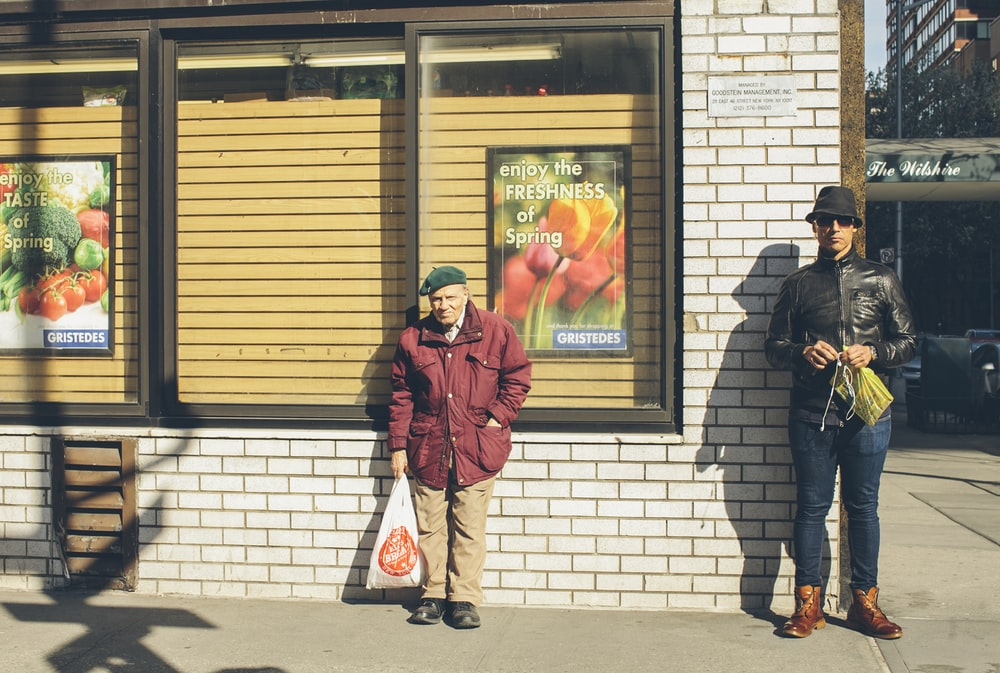 man standing near another man beside building