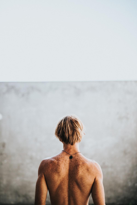 half naked man facing wall