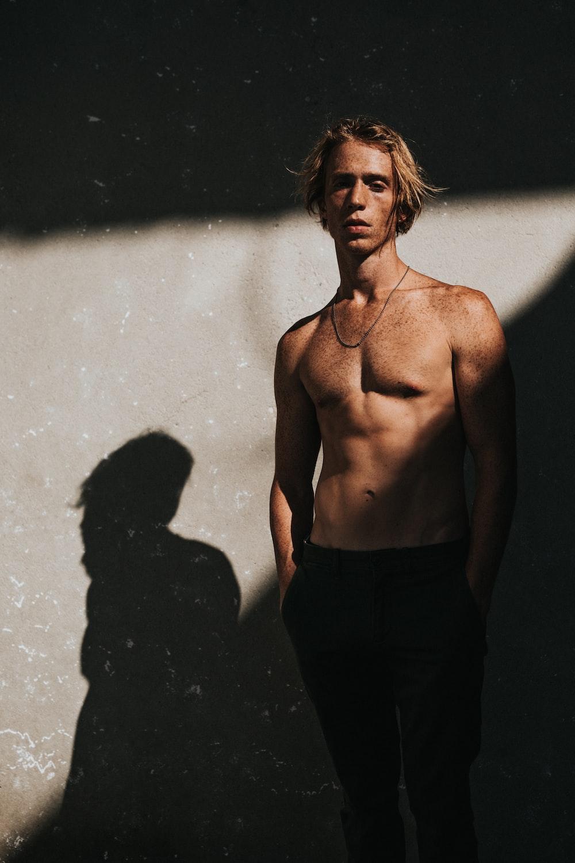 topless man standing near wall