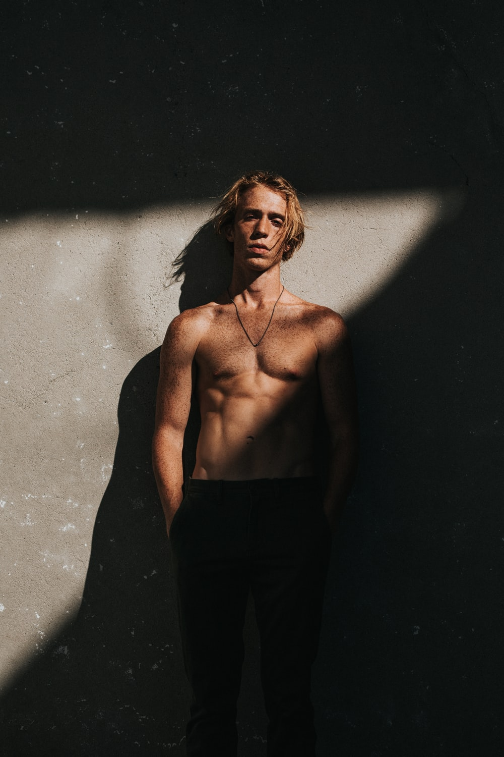 half naked man stands with back on wall