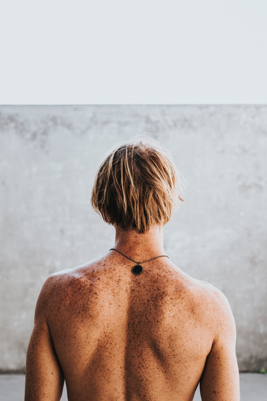 half naked man faces wall
