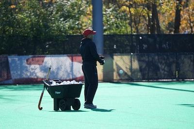 man standing beside wheelbarrow field hockey teams background