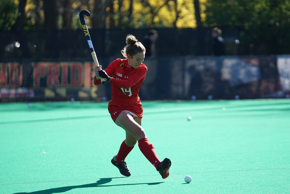 woman playing hockey on fields during daytime