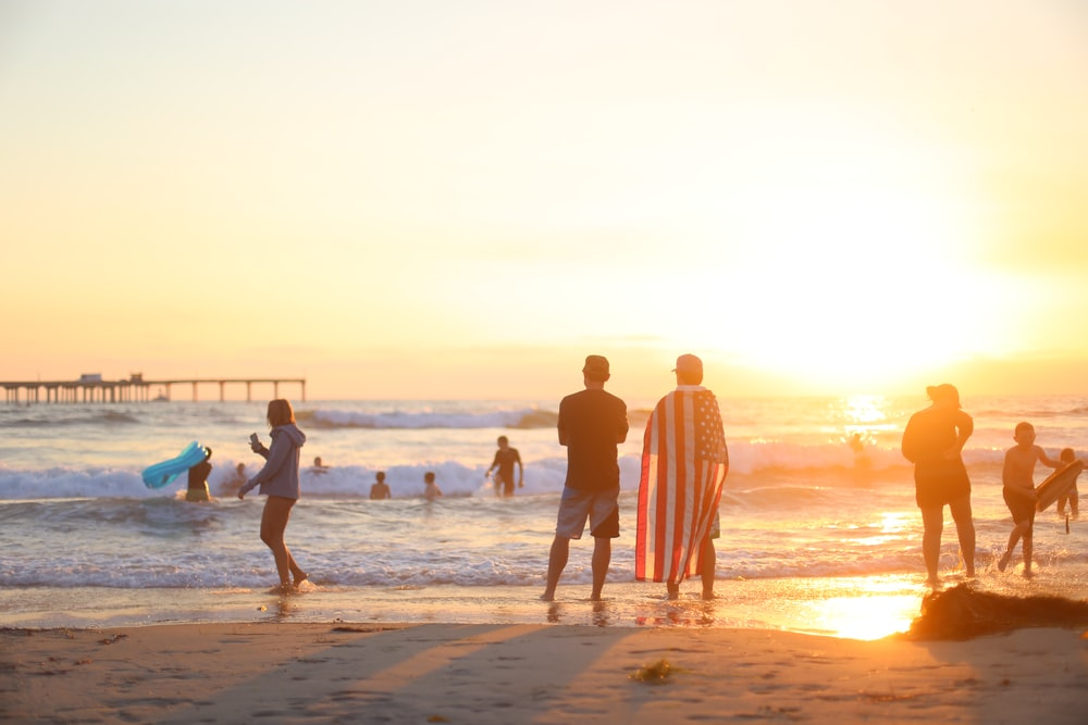 people on beach during golden hour