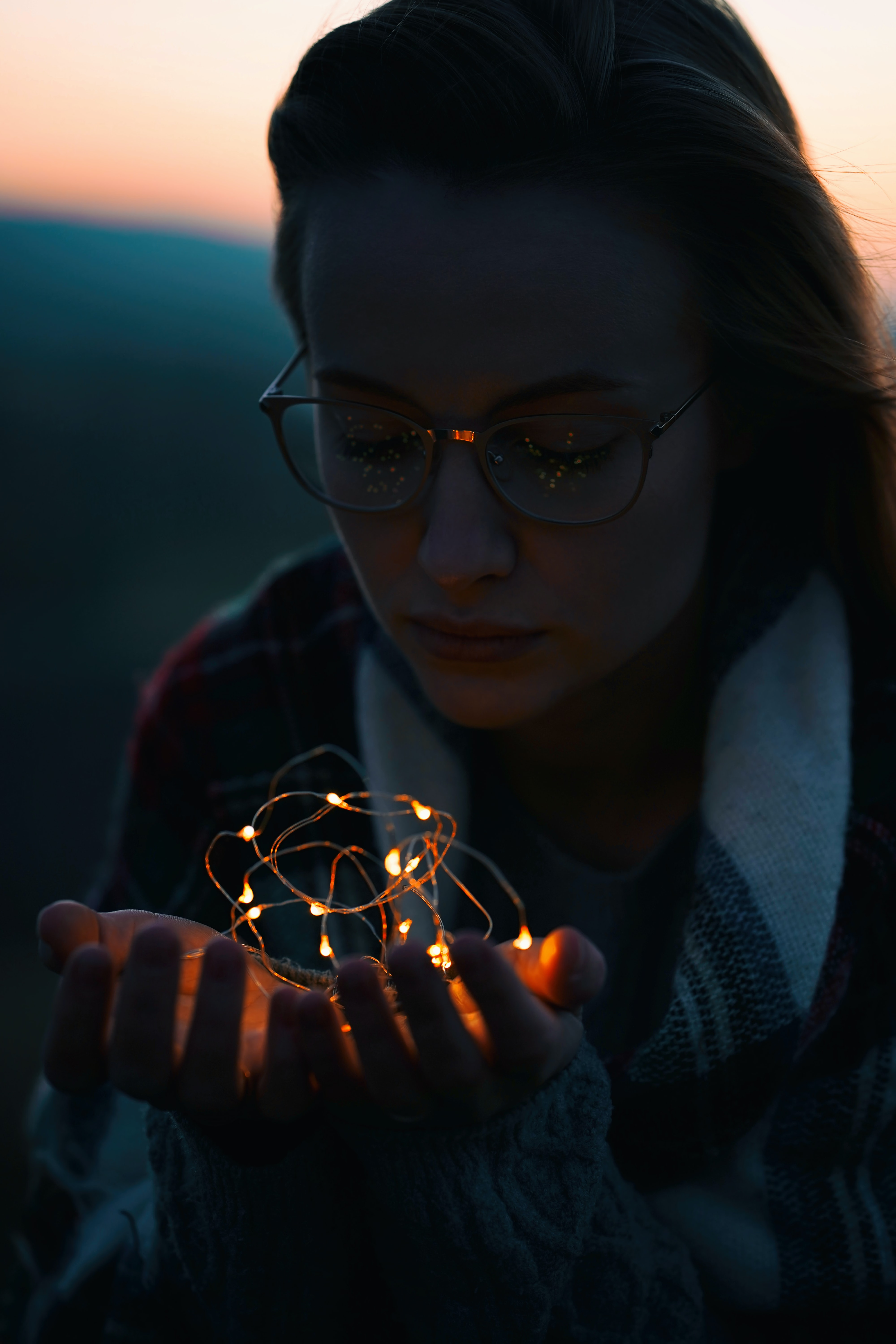 selective focus of woman holding light fixture at night