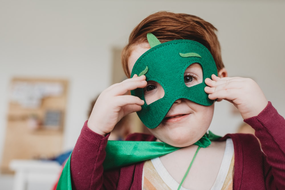 boy holding green mask