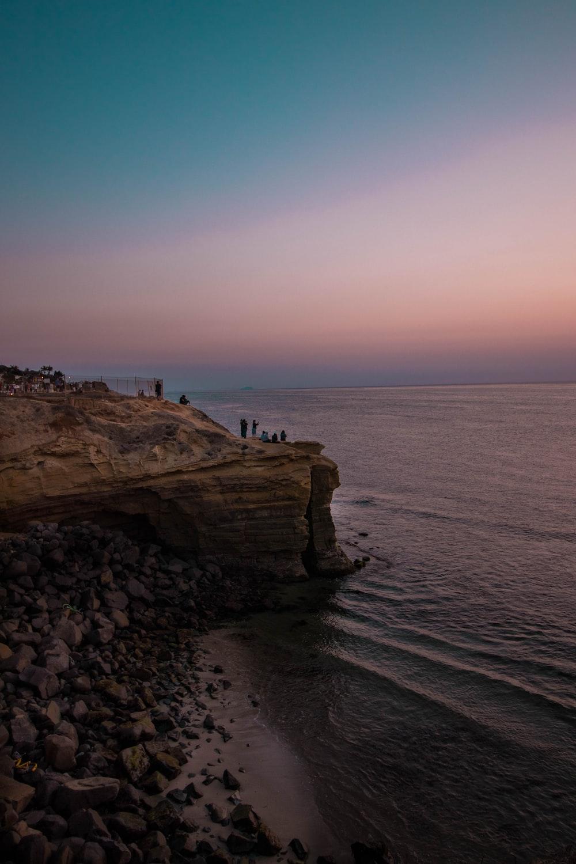 people standing on rockformation near ocean