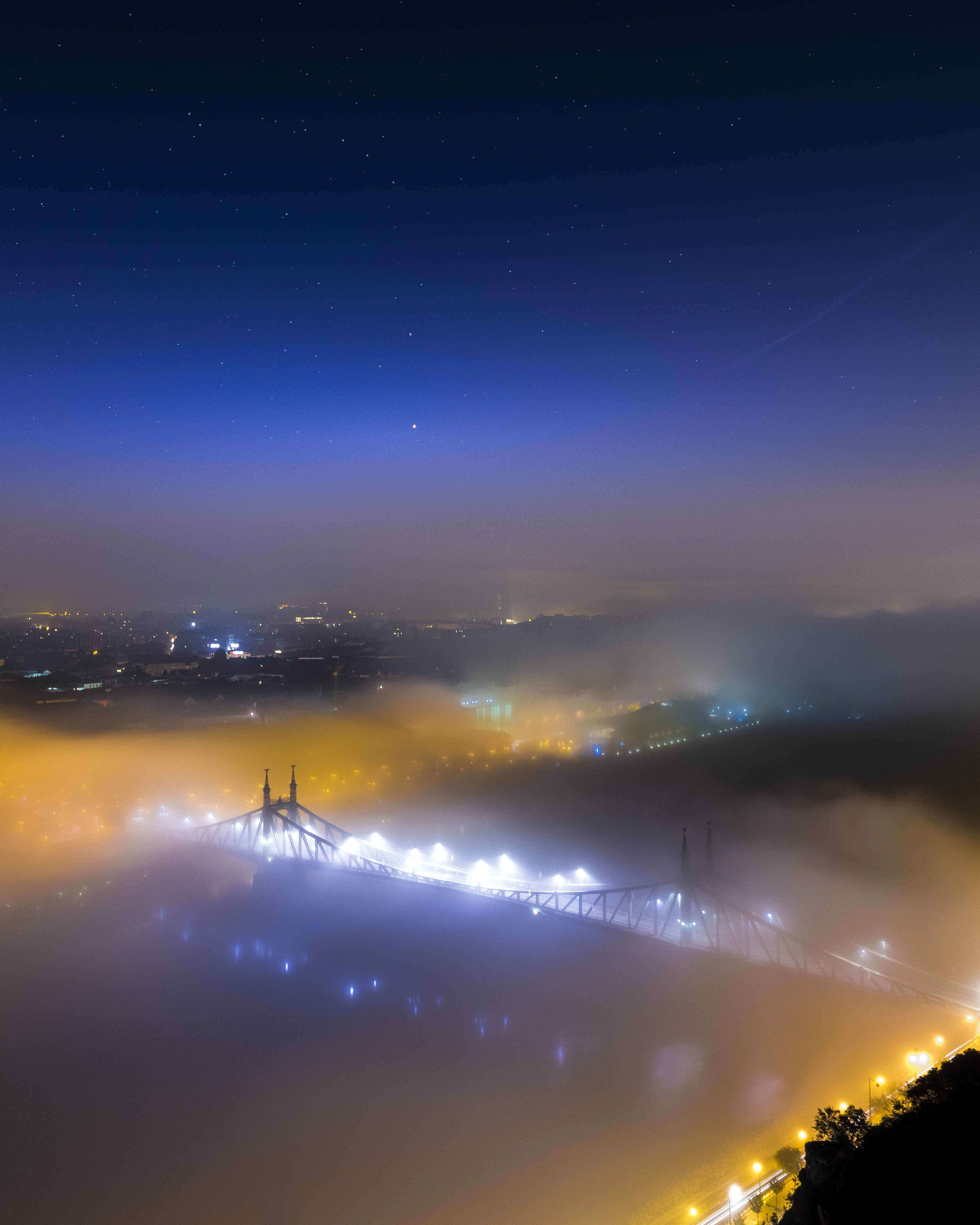 bridge covered with fog during nighttime