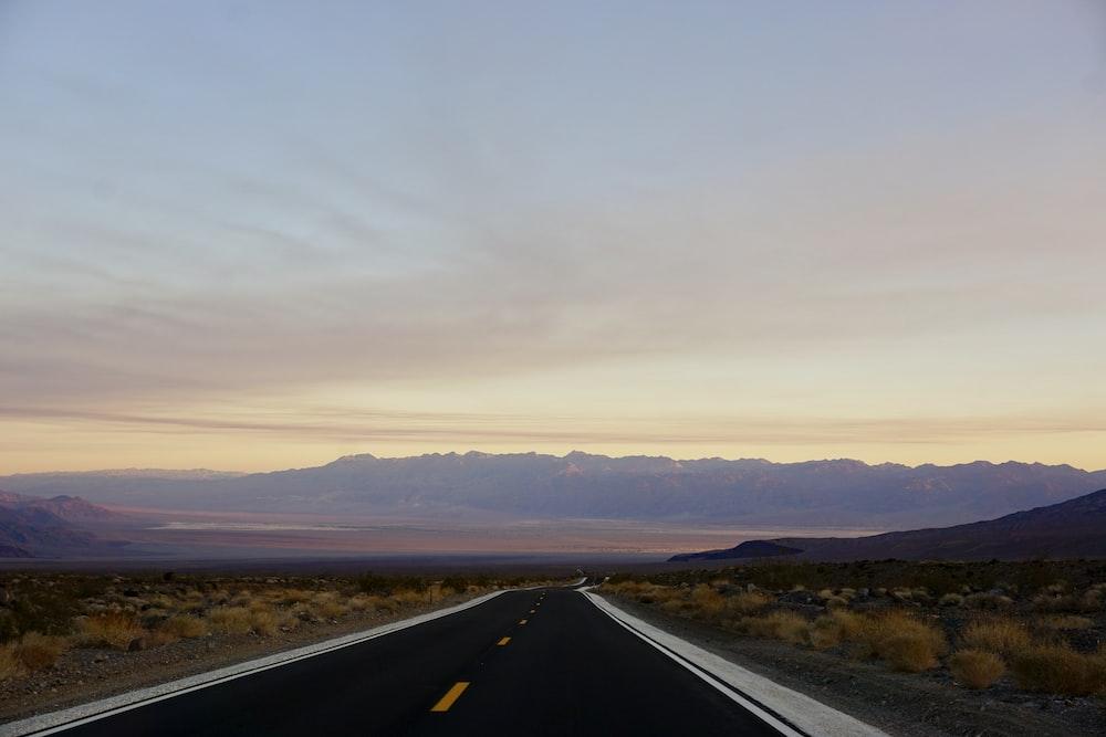 black road under cloudy sky