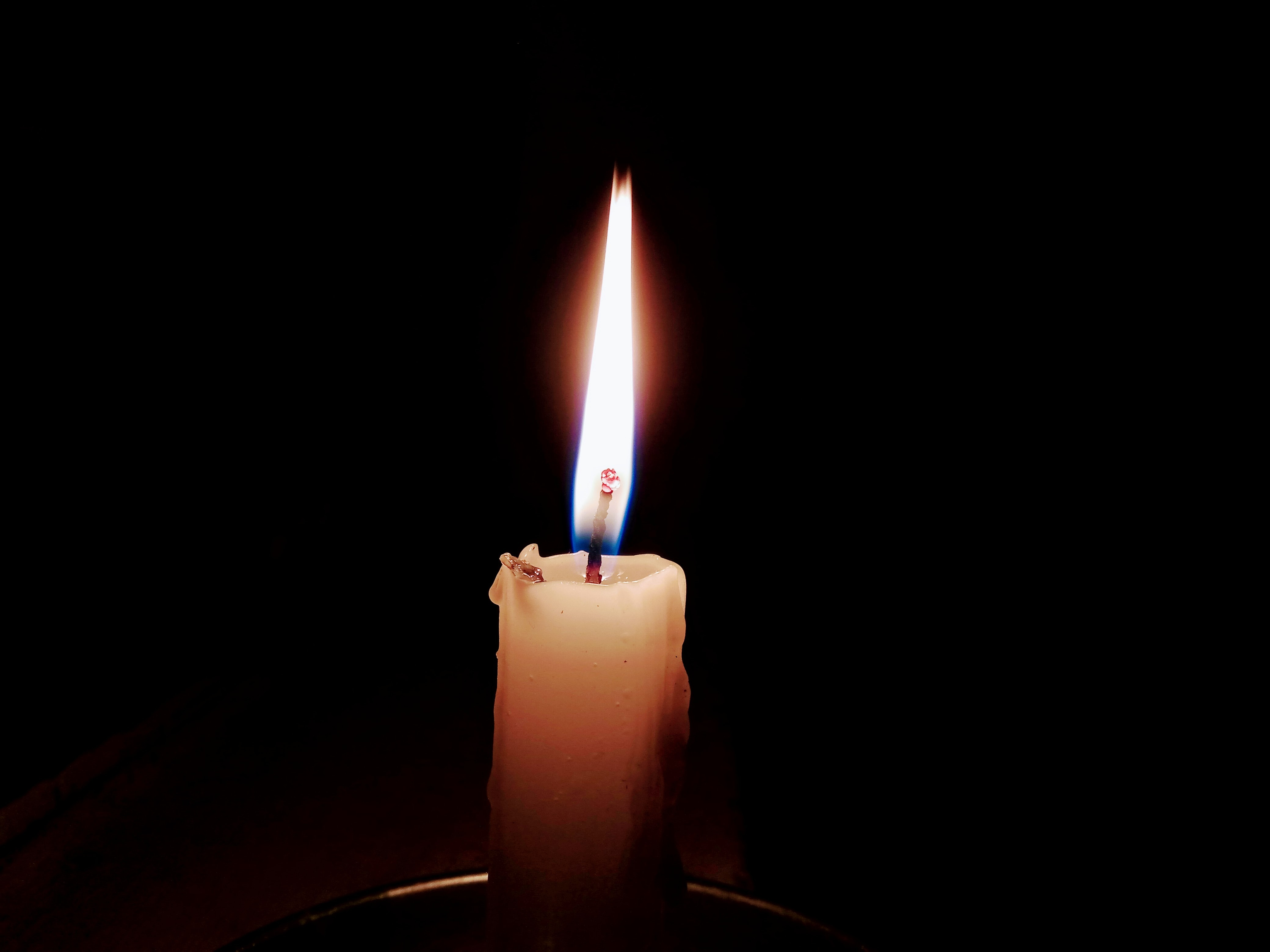 lit candle in focus photography