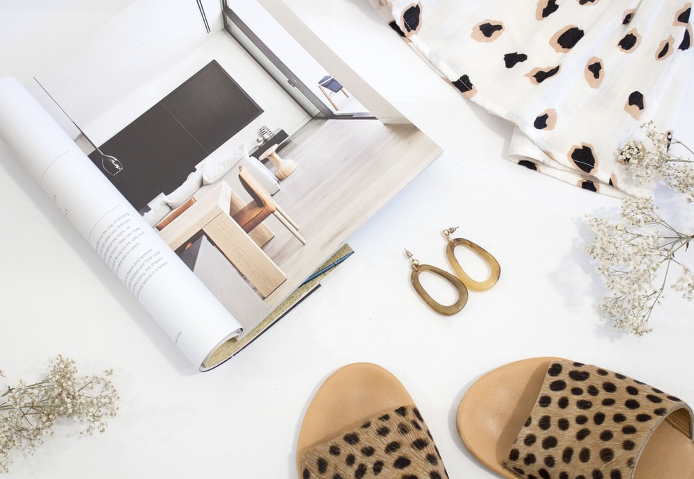 sandals and earrings placed next to opened catalog
