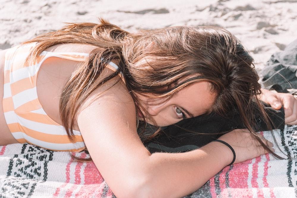 woman lying on beach sand