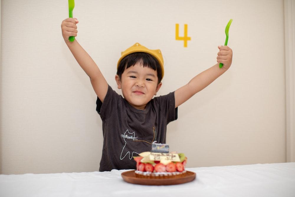 boy raising both his hands