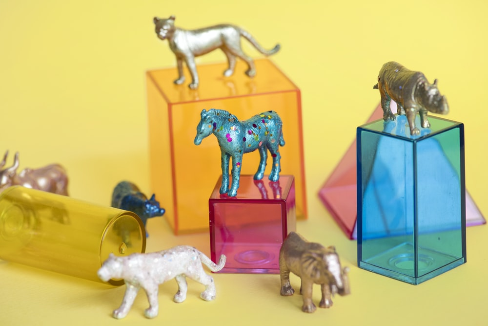 assorted-color-and-kind animal figure lot on yellow surface