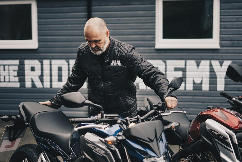 man holding black Honda CB motorcycle