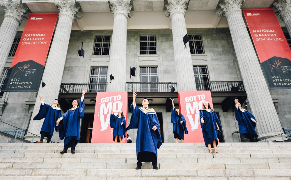 graduates in front of building