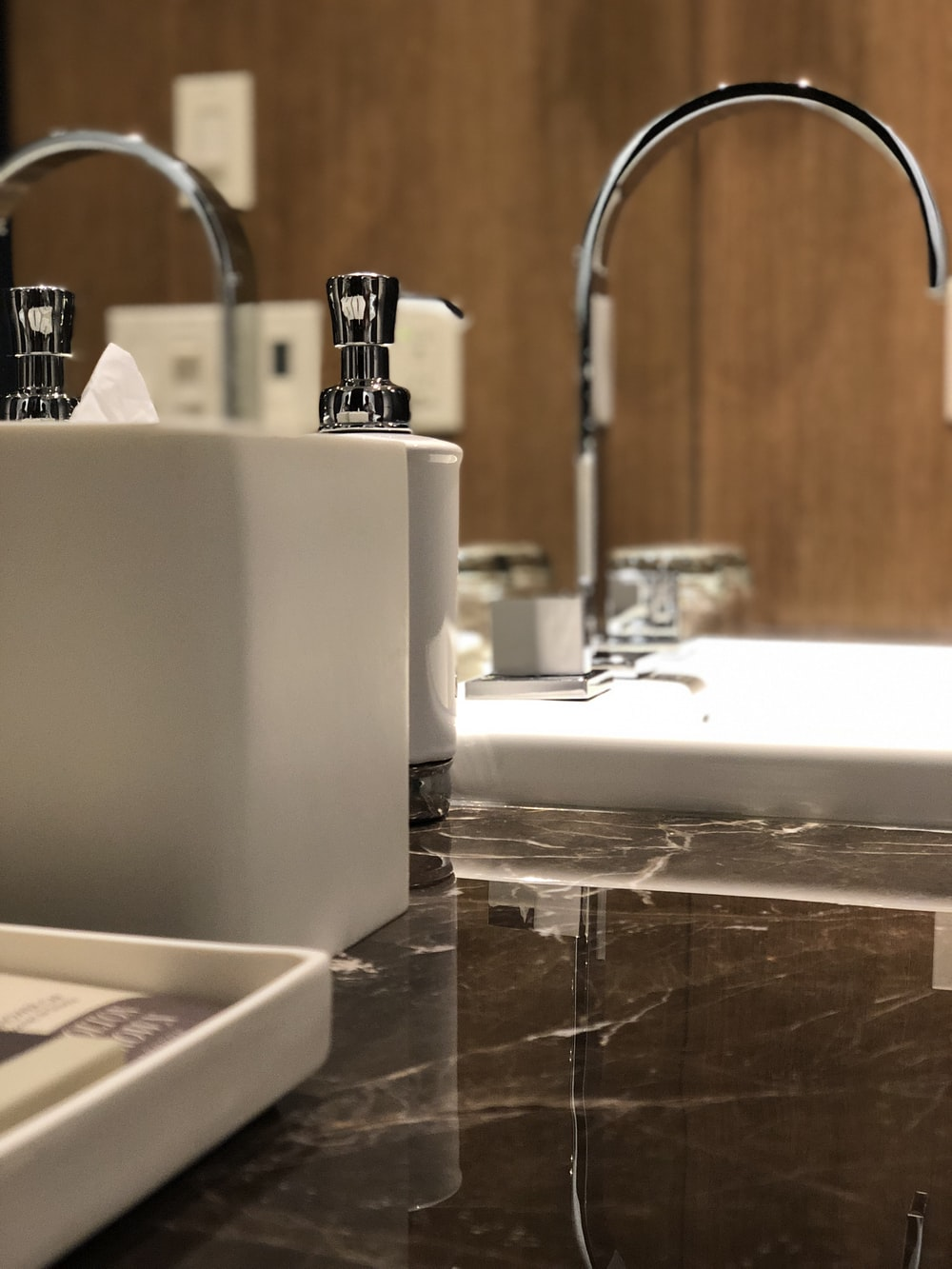 bathroom canisters beside stainless steel faucet