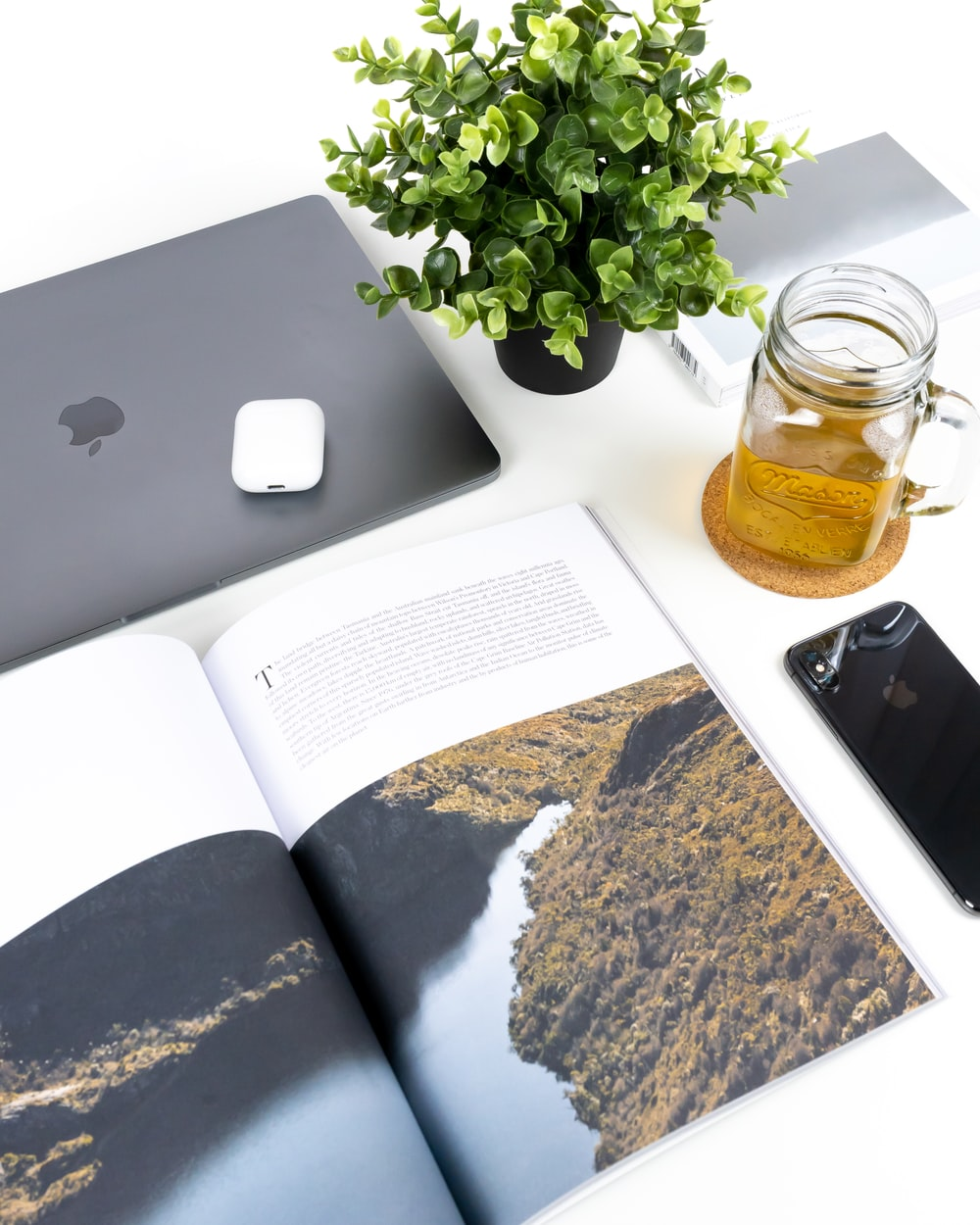 half-empty clear glass jar beside green-leafed plant, MacBook, and space gray iPhone X
