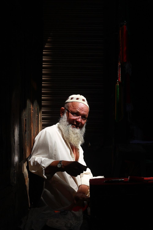 man in white robe sitting on chair
