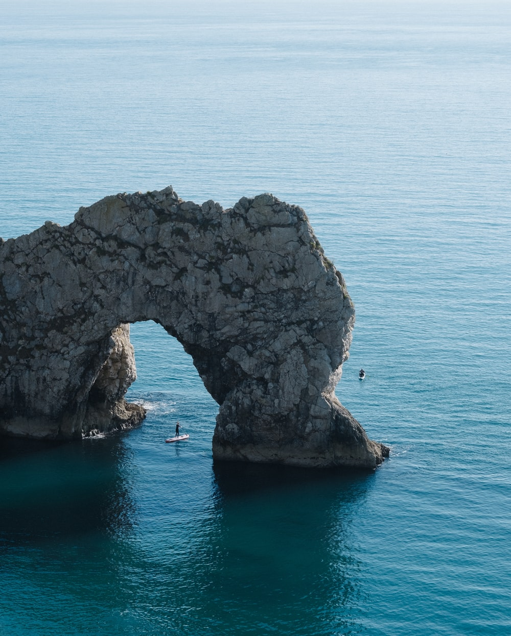 gray stone arch on body of water