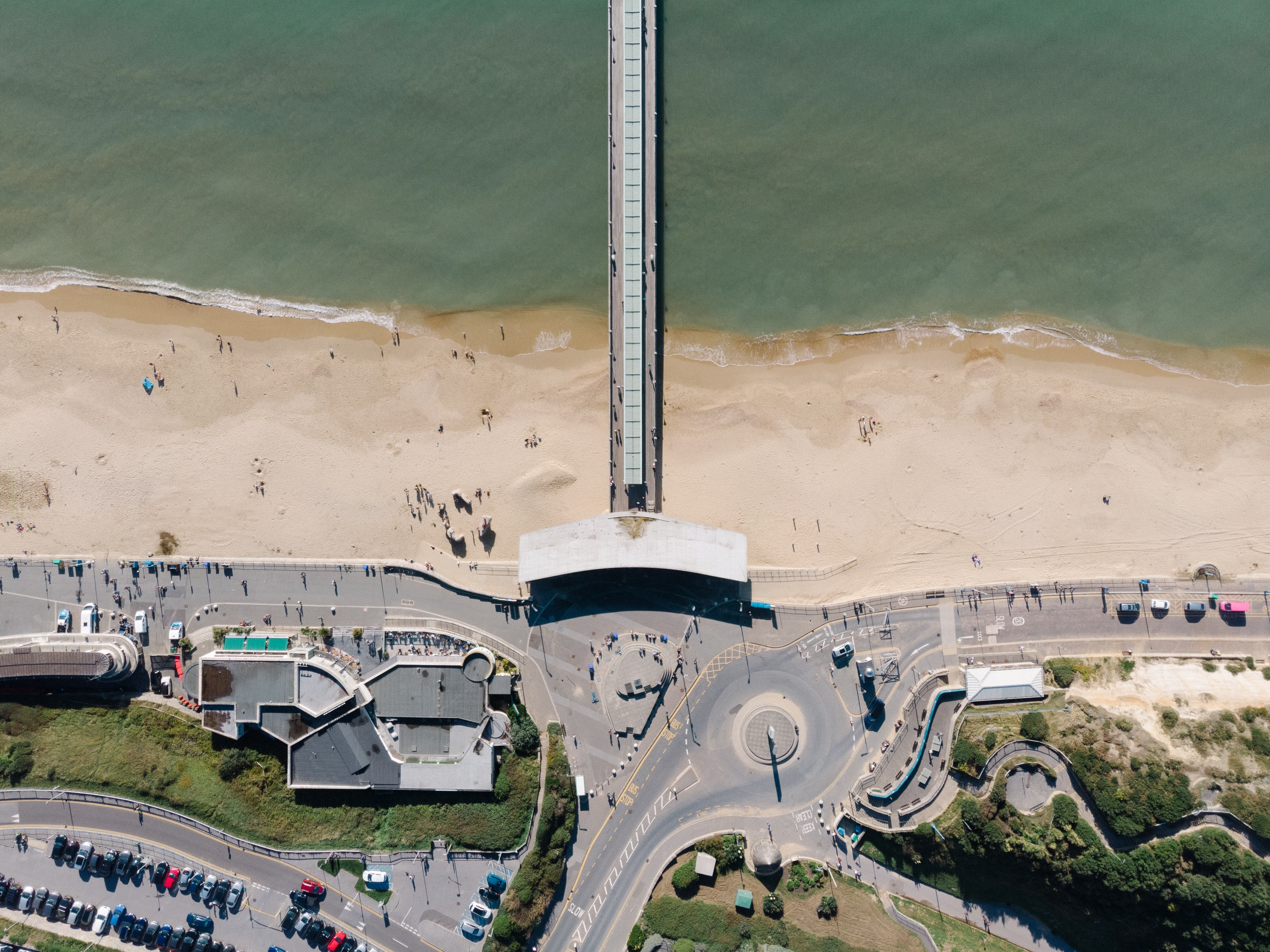 people beside beach and concrete bridge during daytime