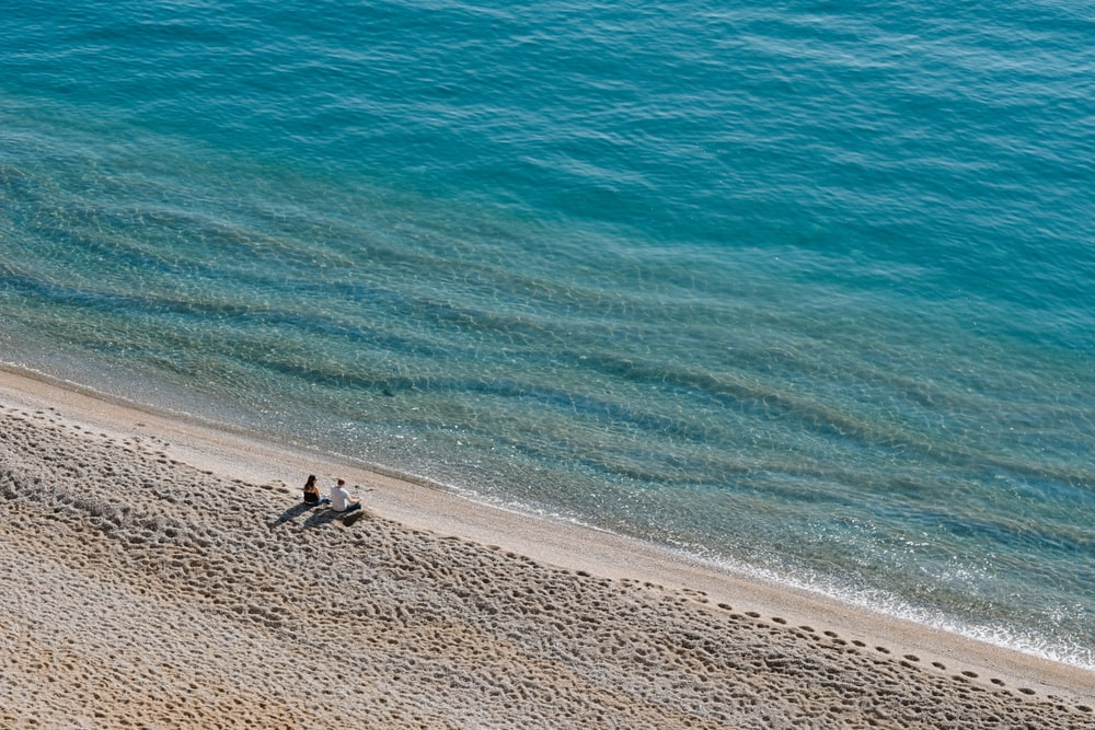 two people sitting on shore